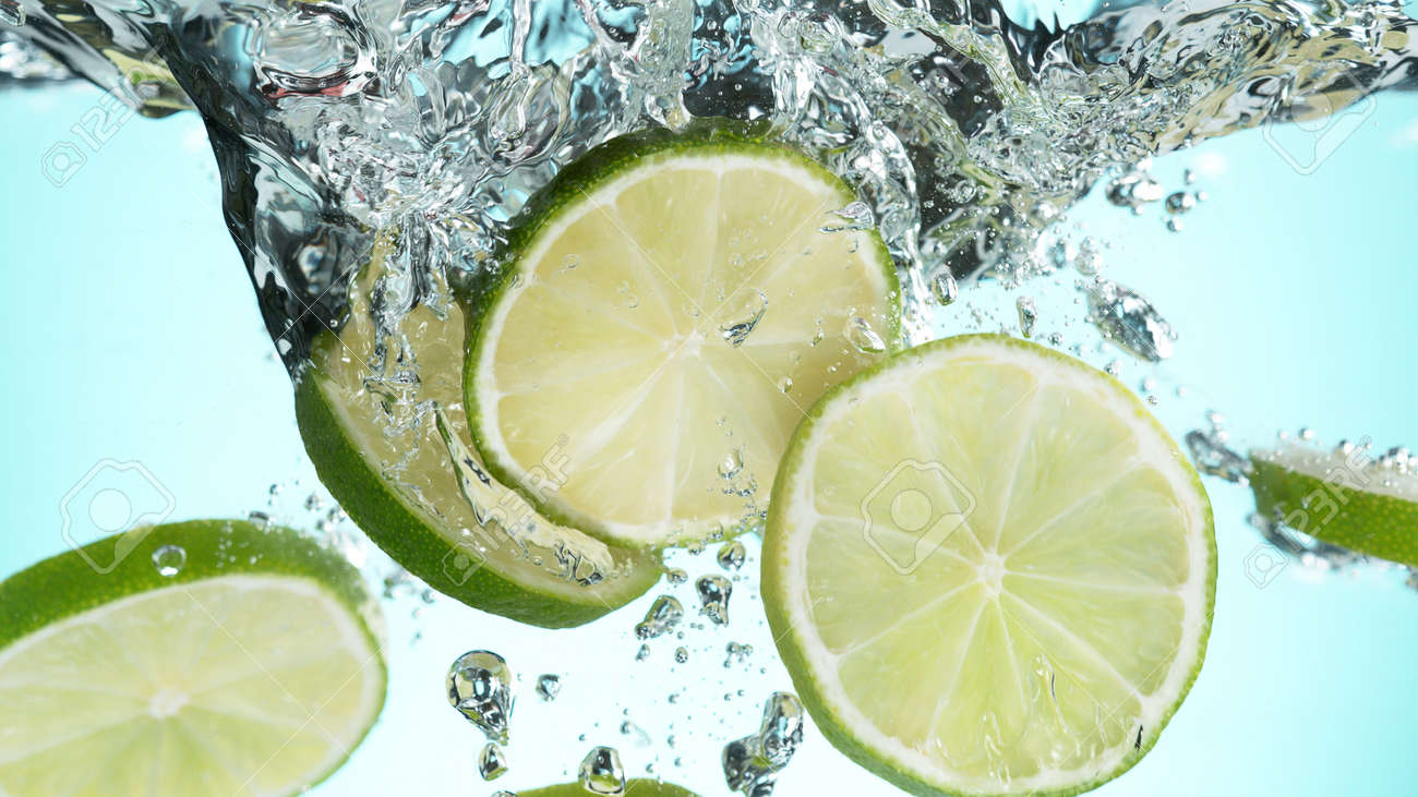 Fresh lime dropped into water with splash and ice cubes. Studio shot with clear background. - 170440786