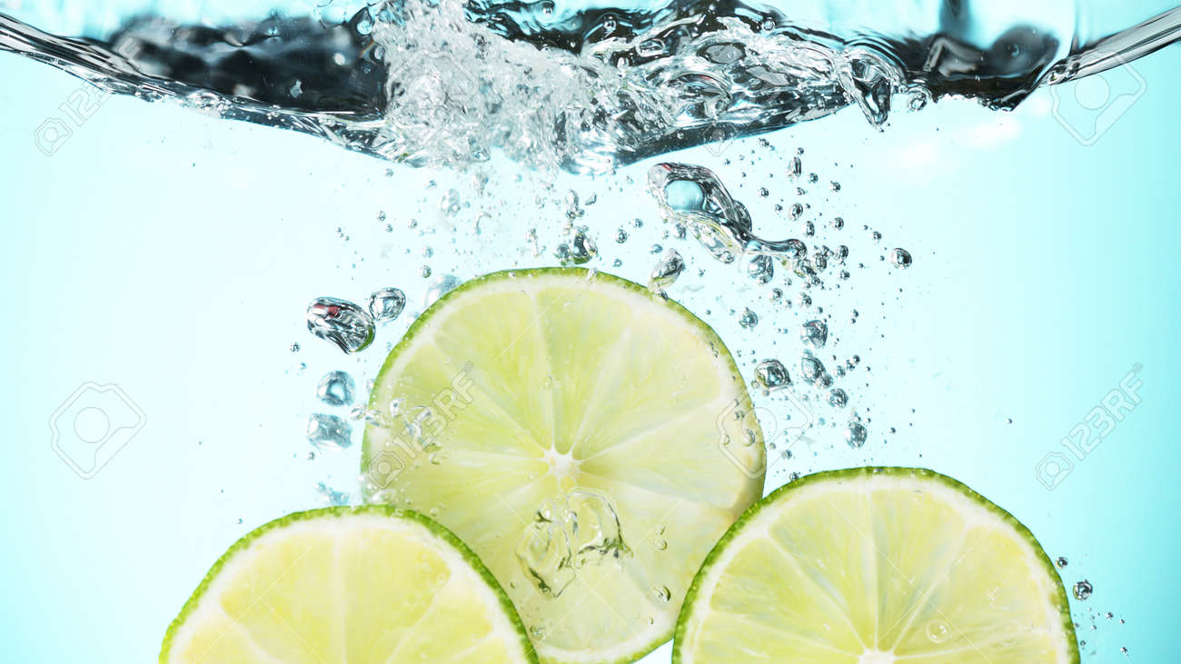 Fresh lime dropped into water with splash and ice cubes. Studio shot with clear background. - 170440550