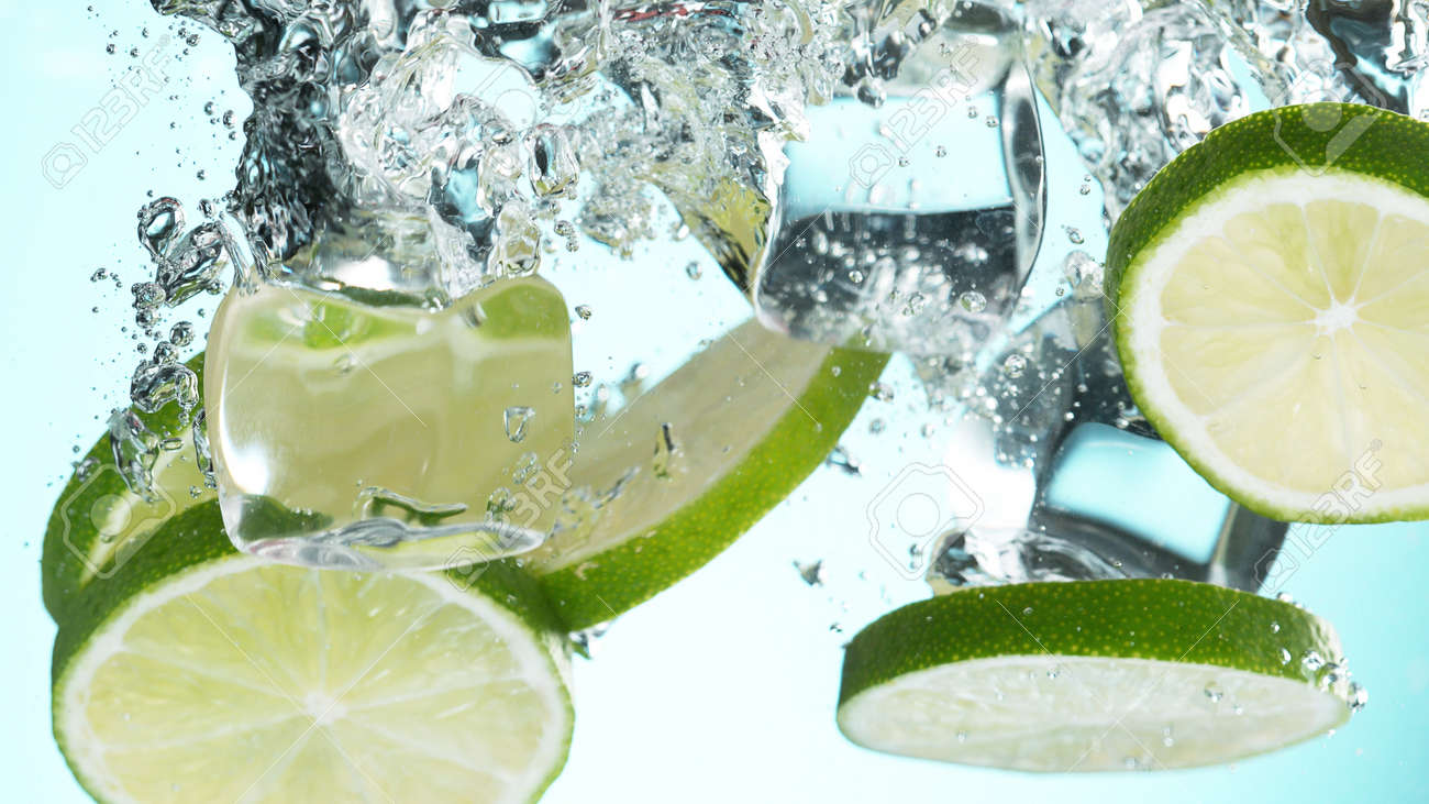 Fresh lime dropped into water with splash and ice cubes. Studio shot with clear background. - 170440452