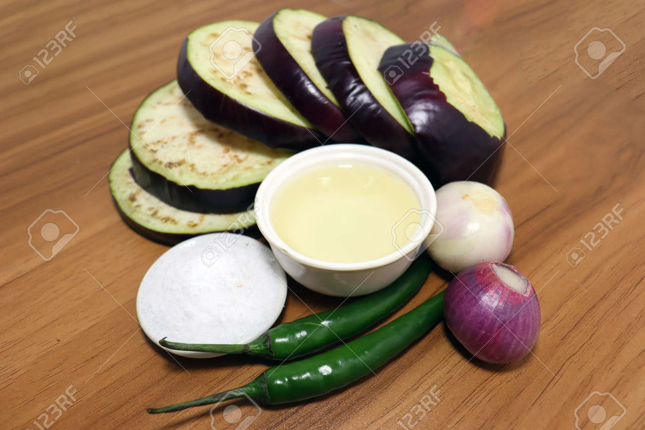 tasty and healthy violet colored Brinjal with spices on wooden table for cooking - 170868002