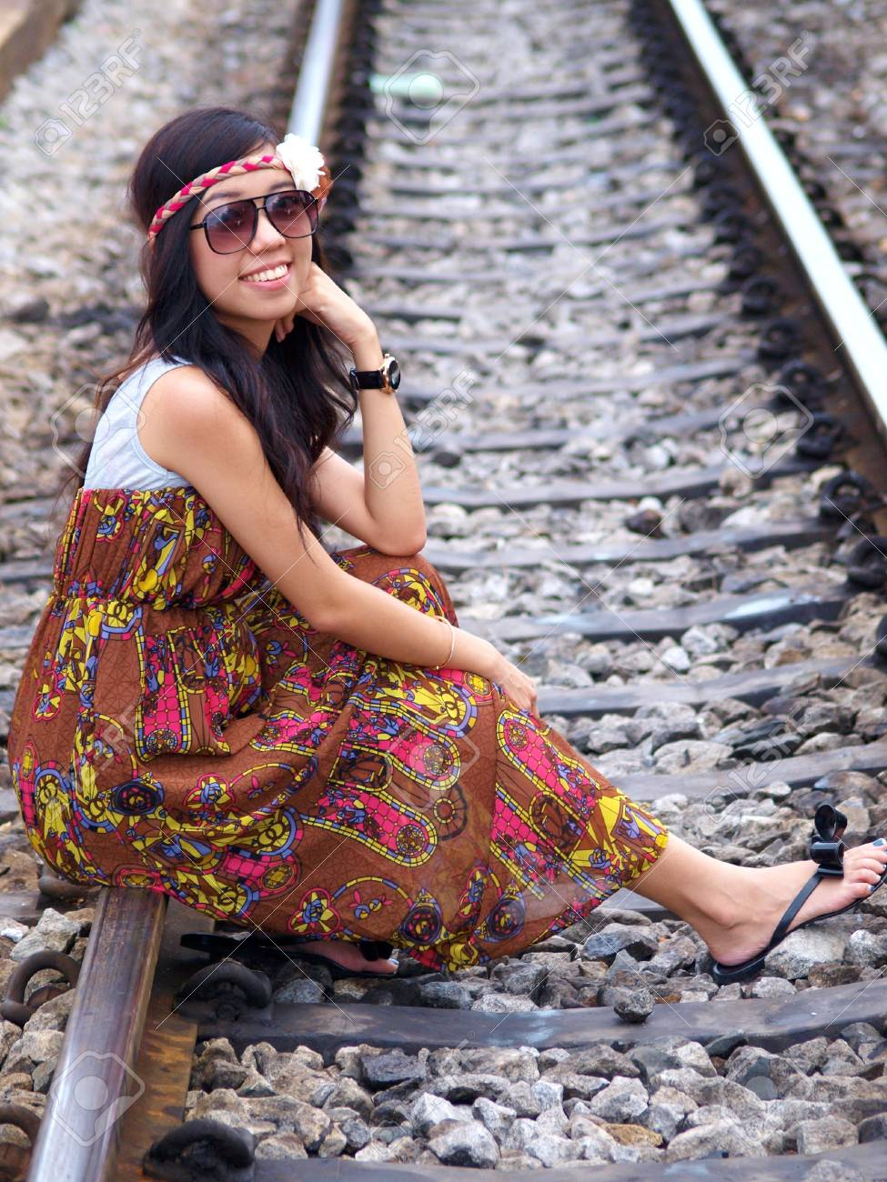 Young pretty Asian girl sitting on railway Stock Photo - 12872865
