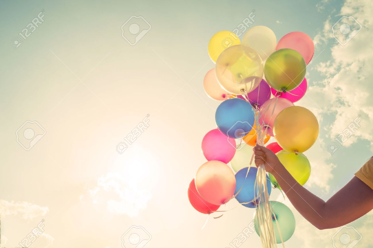 Girl hand holding multicolored balloons done with a retro vintage instagram filter effect, concept of happy birthday in summer and wedding honeymoon party (Vintage color tone) Stock Photo - 51655330