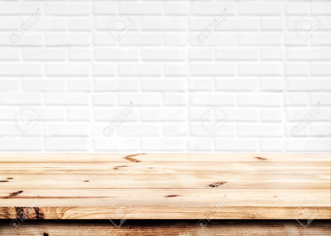 Empty wooden table for product placement or montage with focus to the table top in the foreground, with white brick wall background. - 52070148