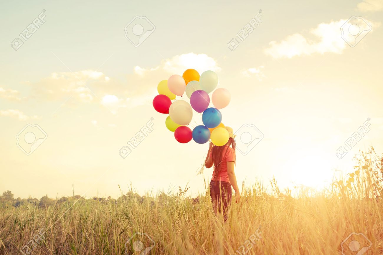 Happiness teen girl with colorful balloons enjoy in the sundown time at grassland. Happy birthday party. vintage color tone effect - 52070162