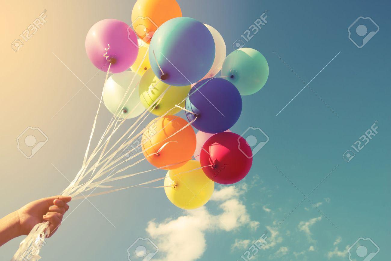 Niña de la mano que sostiene los globos multicolores hechas con un efecto retro filtro de Instagram, el concepto de nacimiento día feliz en el verano y parte de luna de miel de la boda (tono de color de época) Foto de archivo - 52175178