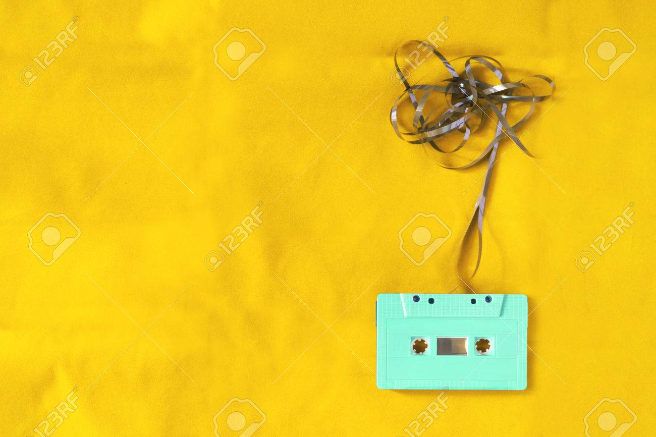 Top view of cassette tape over yellow background with tangled ribbon. retro filter effect and vintage style - 59862939