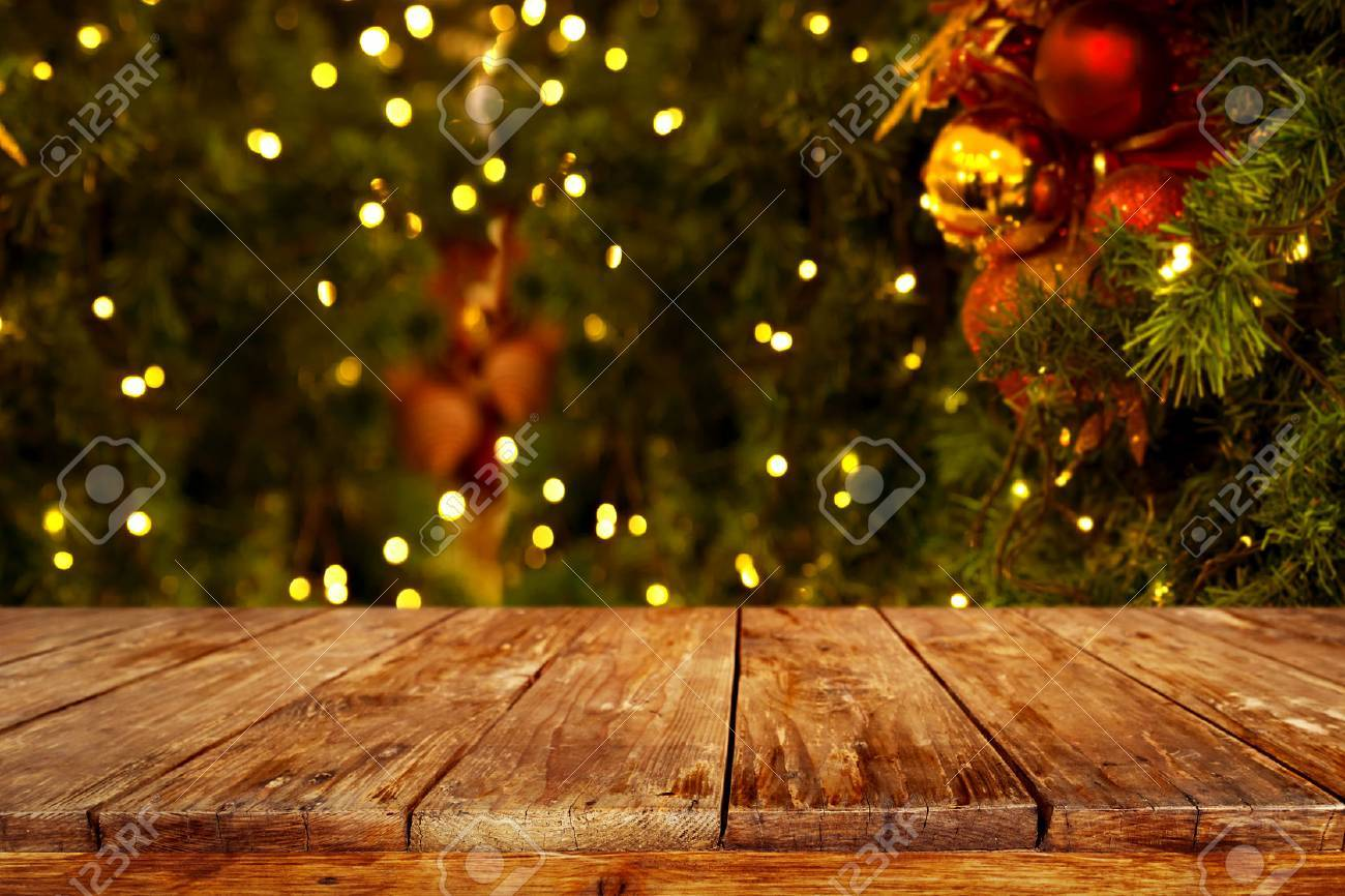 christmas and new year background with empty dark wooden deck table over christmas tree and blurred