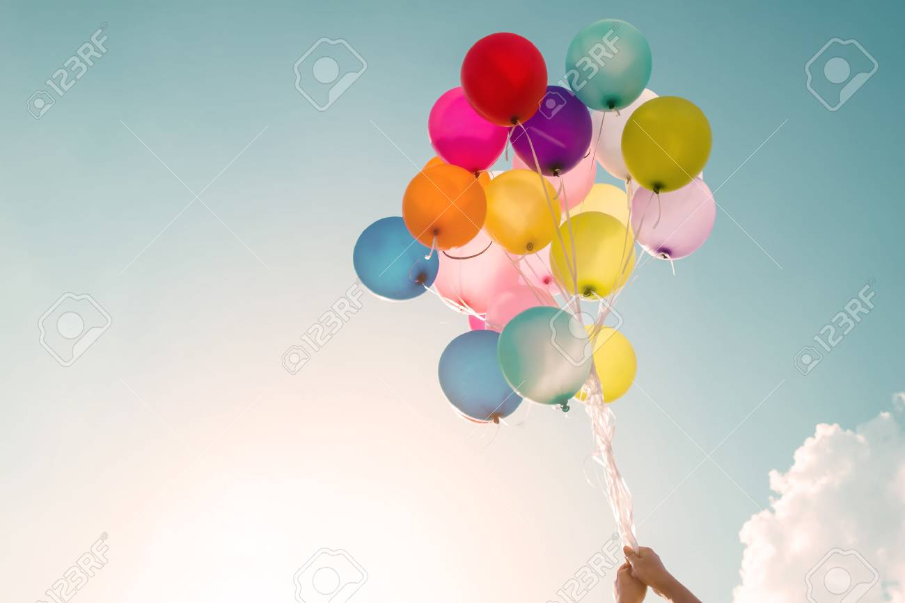 Hands of girl holding multicolored balloons done with a retro vintage filter effect, concept of happy birthday in summer and wedding honeymoon party (Vintage color tone) - 64816019