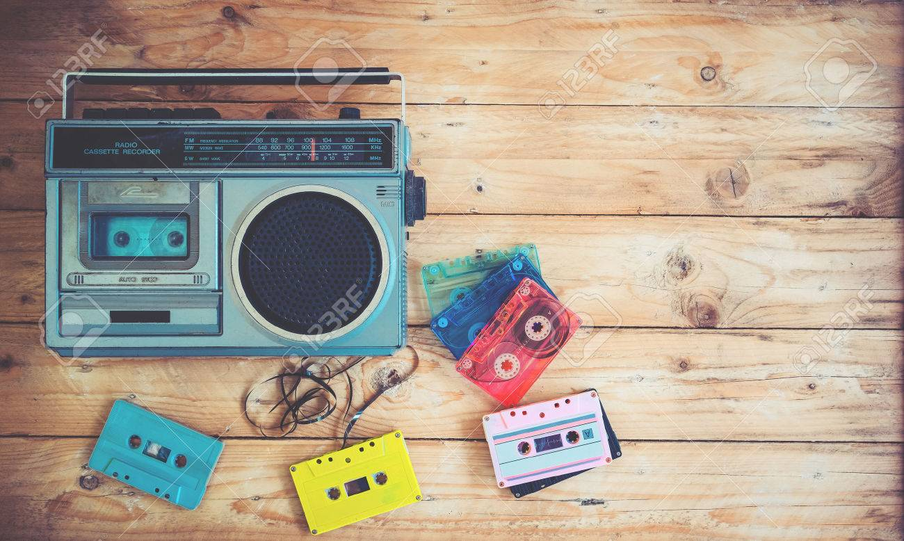 Top view hero header - retro technology of radio cassette recorder music with retro tape cassette on wood table. Vintage color effect styles. Stock Photo - 78523092