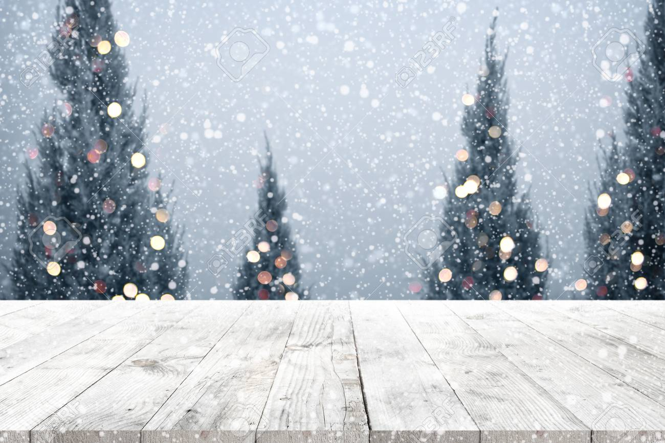 christmas and new year background with wooden deck table over christmas tree snow and blurred
