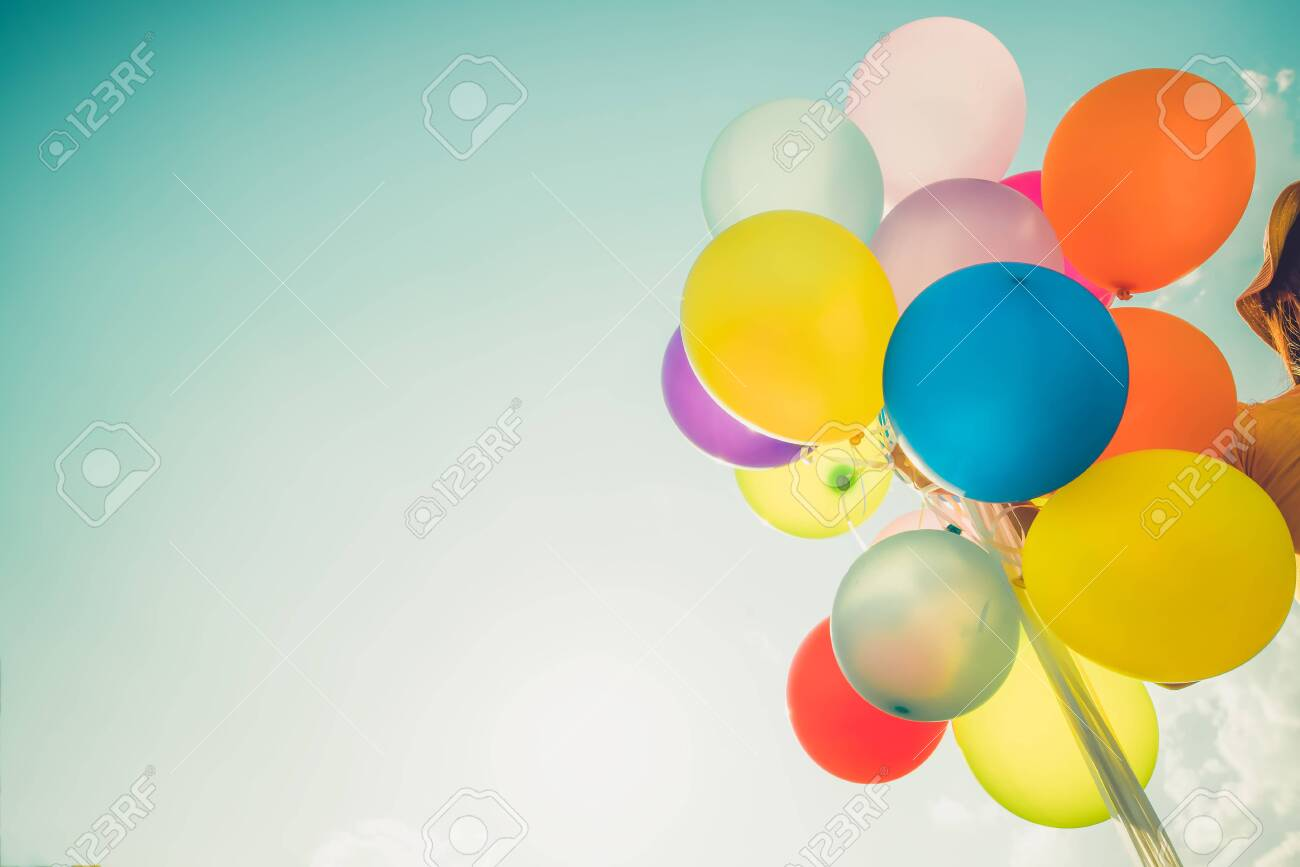 Girl hand holding multicolor balloons done with a retro photo filter effect, concept of happy birth day in summer and wedding honeymoon party, Vintage color tone style - 125946260