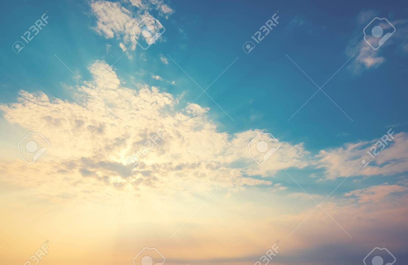 yellow sunlight of the sun through the clouds over the blue sky. sunshine in morning. vintage color effect - 145657152