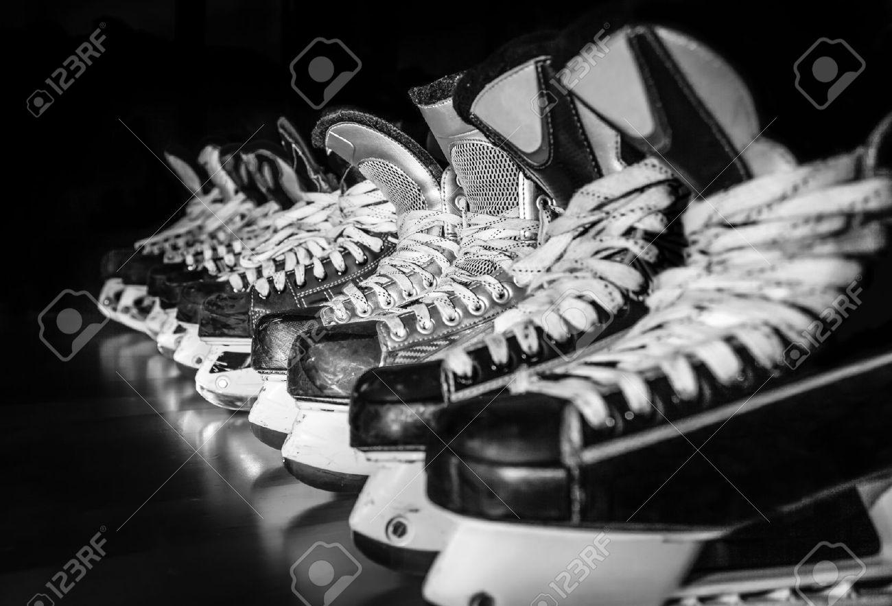 pairs of hockey skates lined up in a locker room stock photo