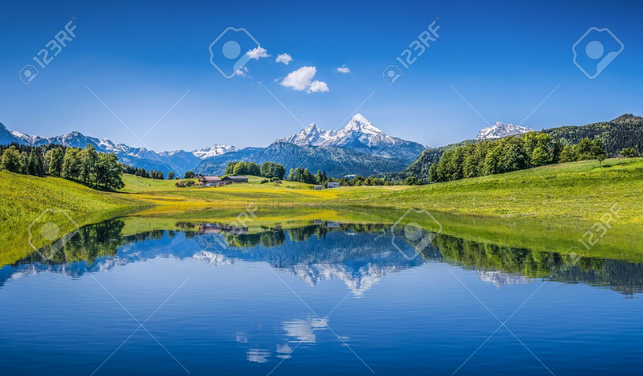 Panoramic view of idyllic summer landscape in the Alps with clear mountain lake and fresh green mountain pastures in the background - 47650083