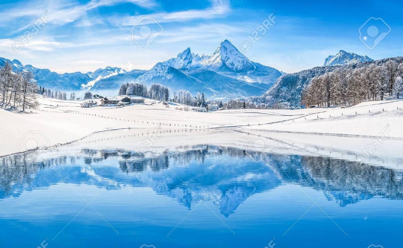 Winter wonderland scenery in the Alps with snowy mountain summits reflecting in crystal clear mountain lake on a cold sunny day with blue sky and clouds - 49066417