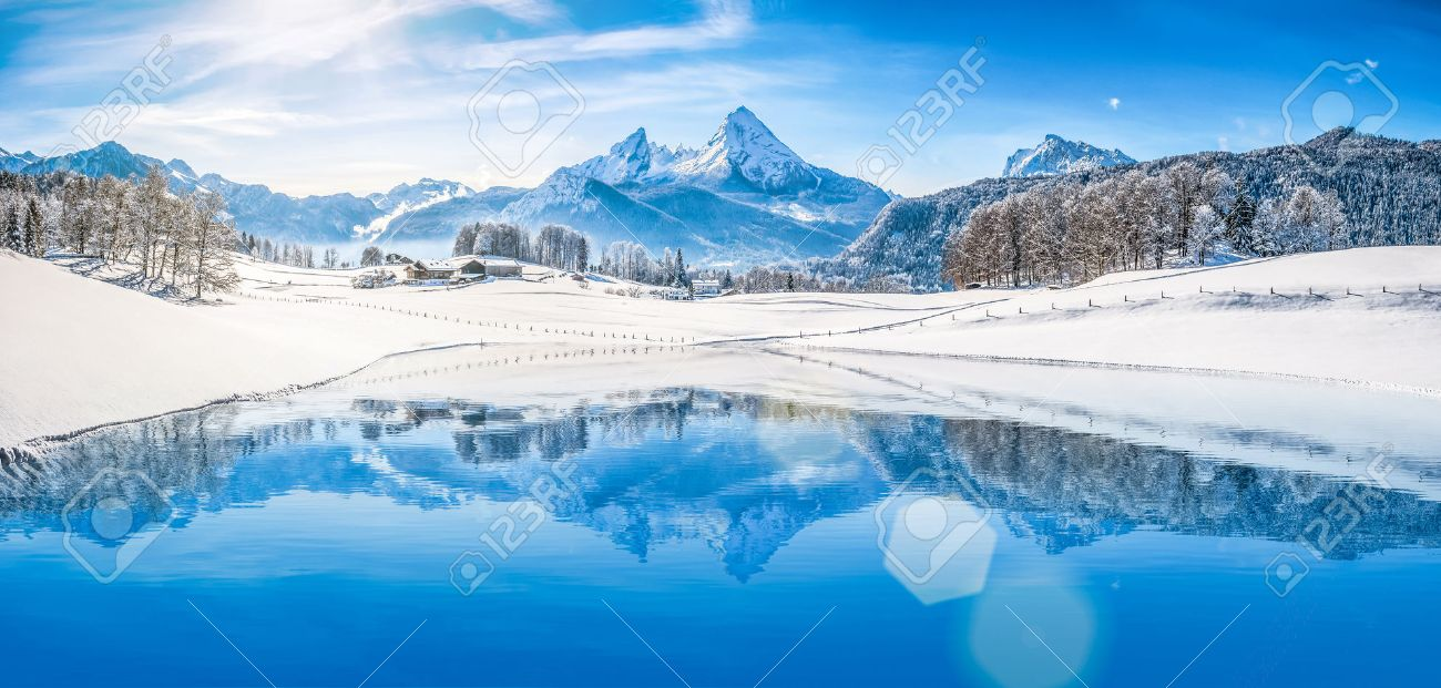 Panoramic view of beautiful white winter wonderland scenery in the Alps with snowy mountain summits reflecting in crystal clear mountain lake on a cold sunny day with blue sky and clouds - 49066371