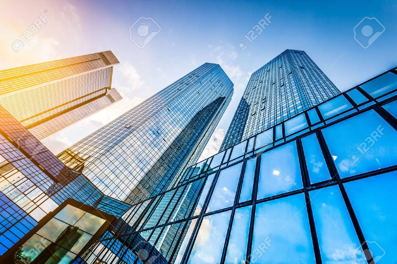 Vue de dessous de gratte-ciel modernes dans le quartier d'affaires au coucher du soleil avec effet de filtre lens flare Banque d'images - 55032022