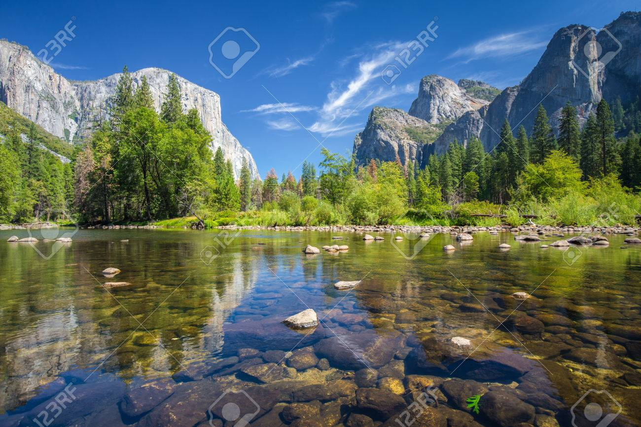 Classic view of scenic Yosemite Valley with famous El Capitan rock climbing summit and idyllic Merced river on a sunny day with blue sky and clouds in summer, Yosemite National Park, California, USA - 76486050