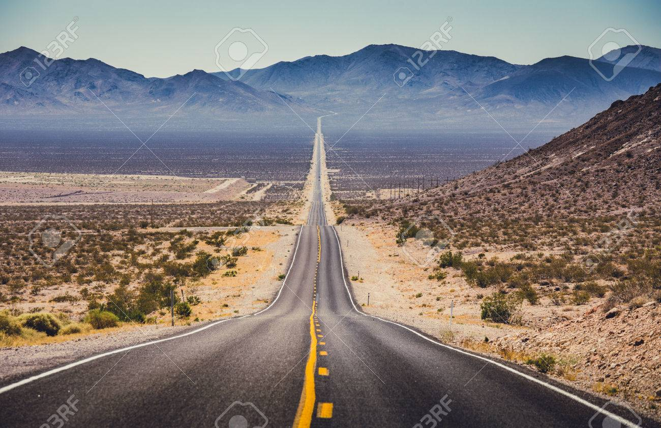Classic panorama view of an endless straight road running through the barren scenery of the American Southwest with extreme heat haze on a beautiful hot sunny day with blue sky in summer - 80060826