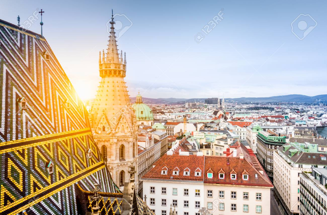 Aerial view over the historical rooftops of Vienna from the north tower of famous St. Stephen's Cathedral in beautiful golden evening light at sunset in summer, central Vienna, Austria - 94397385