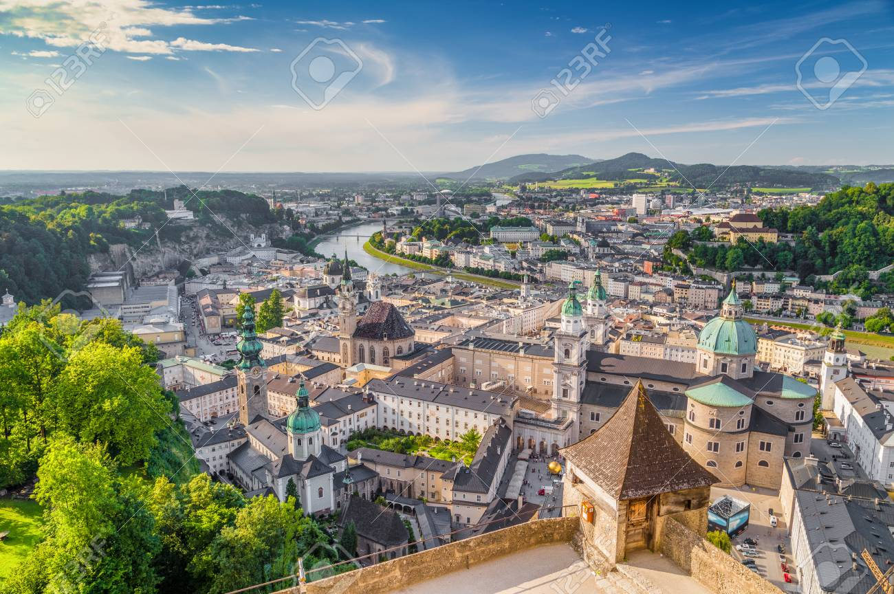 Aerial panoramic view of the historic city of Salzburg with Salzach river in beautiful golden evening light with blue sky and clouds at sunset in summer, Salzburger Land, Austria - 94397589
