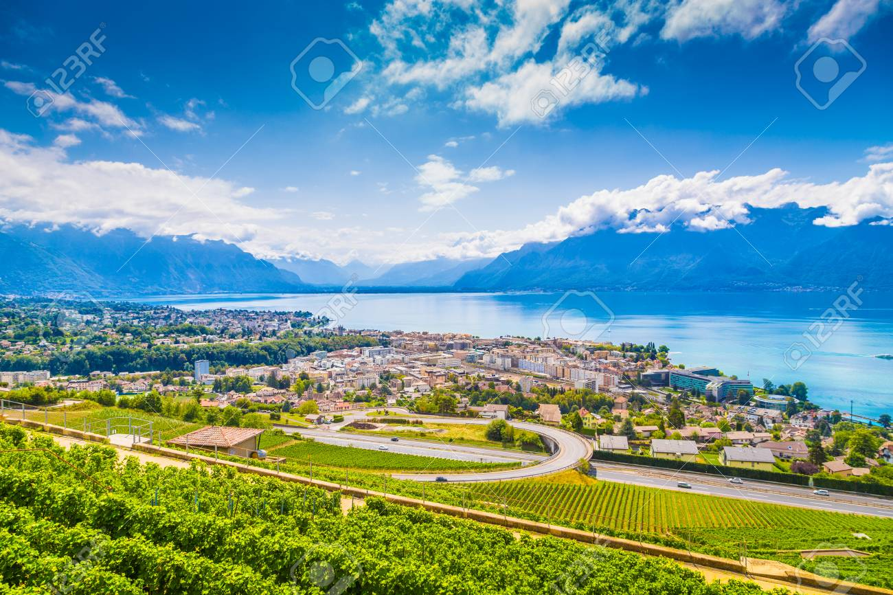 Aerial panoramic view of the city of Vevey at Lake Geneva with vineyards of famous Lavaux wine region on a beautiful sunny day with blue sky and clouds in summer, Canton of Vaud, Switzerland - 94981641