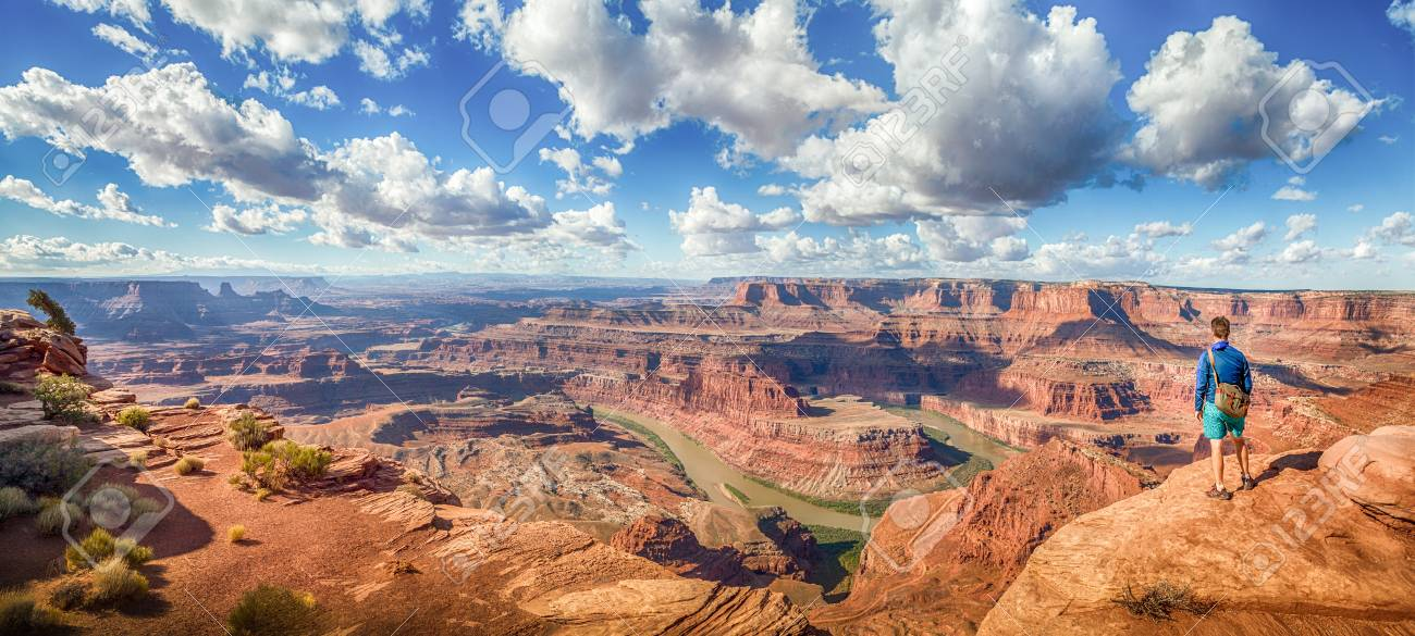 Panoramic view of young hiker standing on a cliff in in scenic Dead Horse Point State Park enjoying the view on a beautiful sunny day with blue sky and dramatic clouds in summer, Utah, USA - 96513640