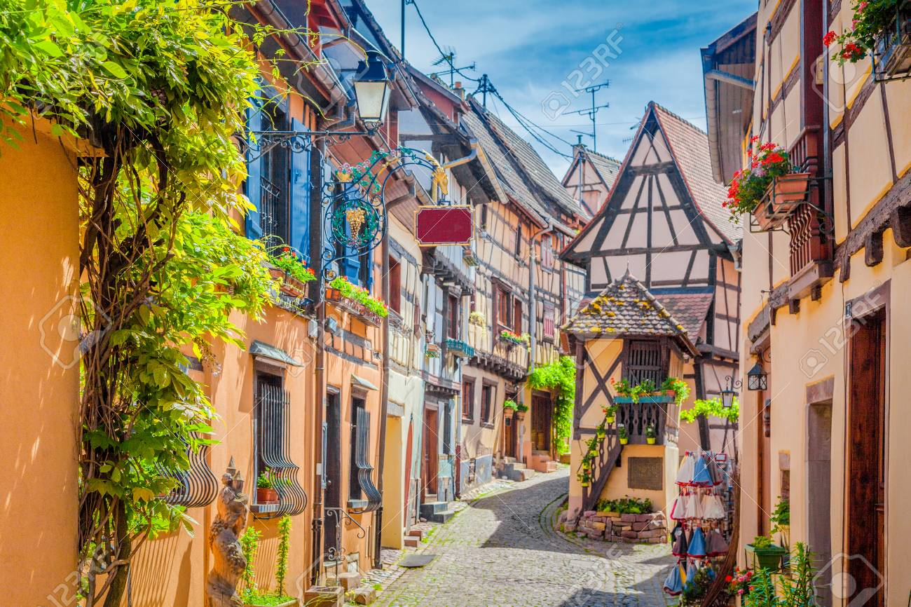 Charming street scene with colorful houses in the historic town of Eguisheim on a beautiful sunny day with blue sky and clouds in summer, Alsace, France - 95429718