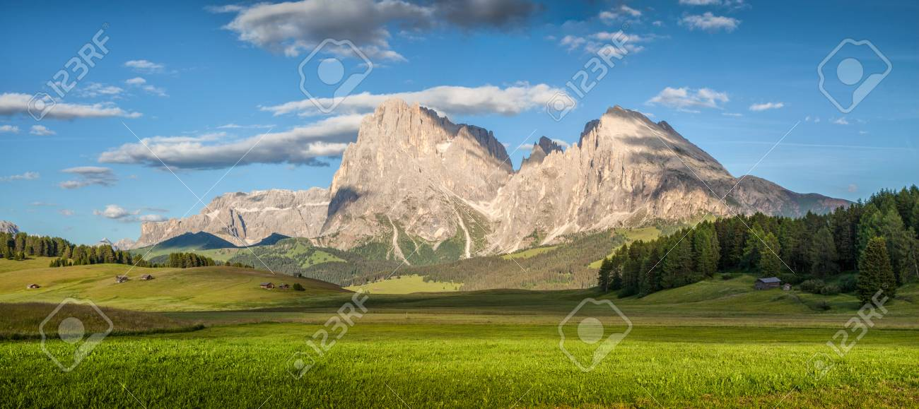 Beautiful view of idyllic alpine mountain scenery with with famous Langkofel mountain summit on a sunny day with blue sky and clouds in springtime, Alpe di Siusi, South Tyrol, Italy - 95465167