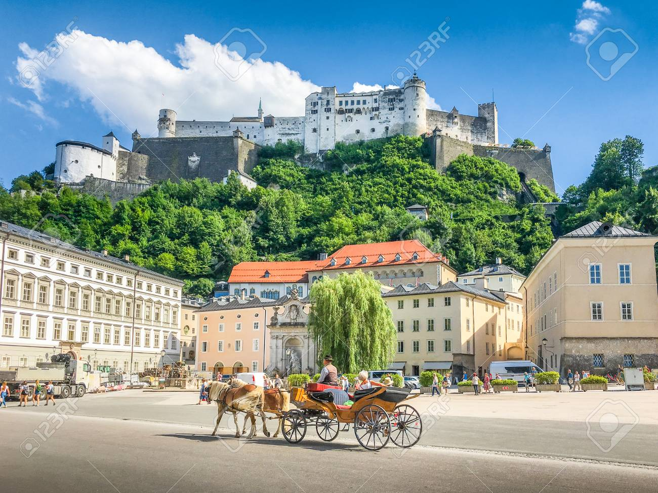 Beautiful panoramic view of the historic city of Salzburg with traditonal horse-drawn Fiaker carriage and famous Hohensalzburg Fortress on a hill on a sunny day with blue sky and clouds in summer - 100199088