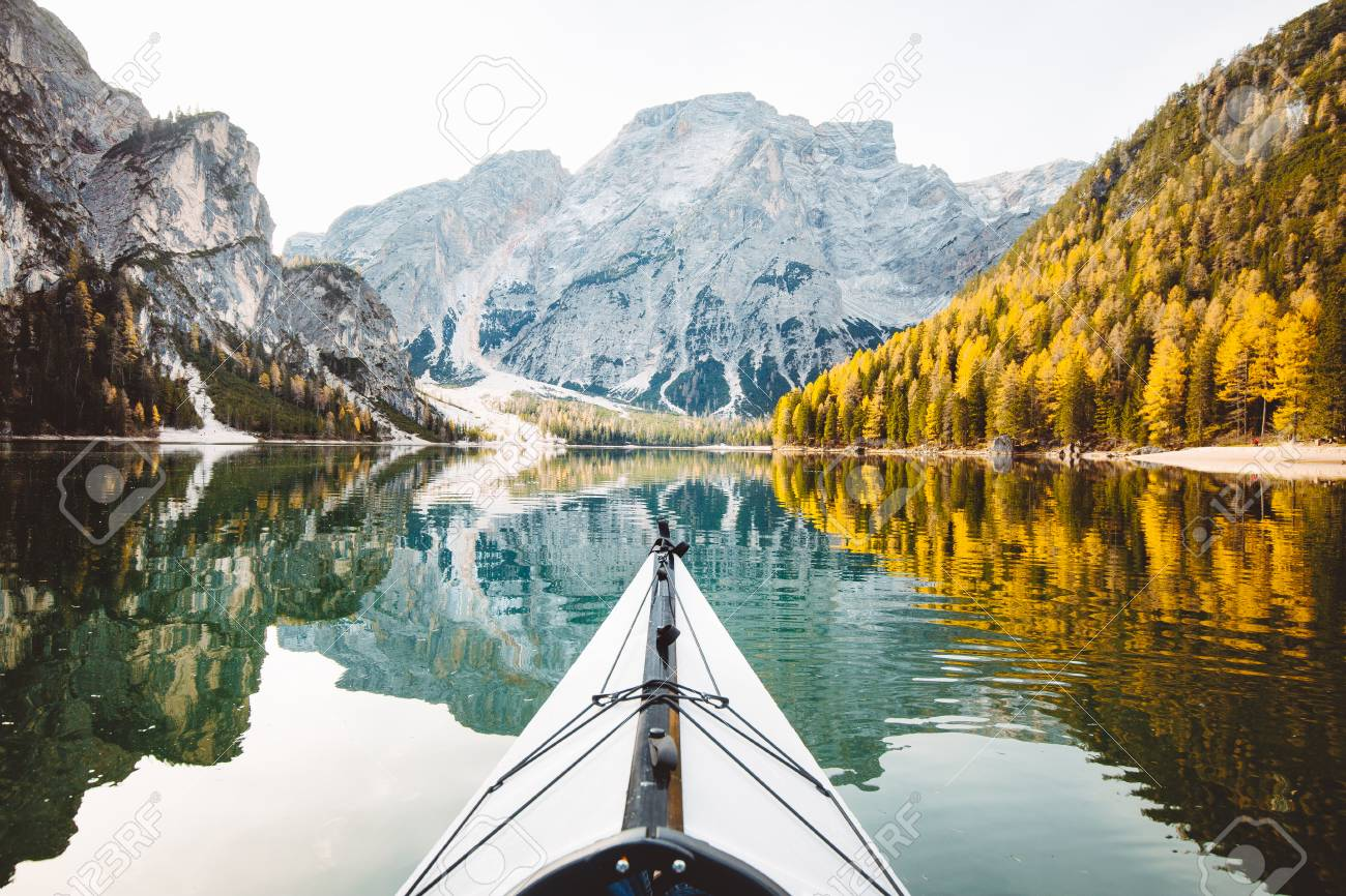 Beautiful view of kayak on a calm lake with amazing reflections of mountain peaks and trees with yellow autumn foliage in fall, Lago di Braies, Italy - 113997392