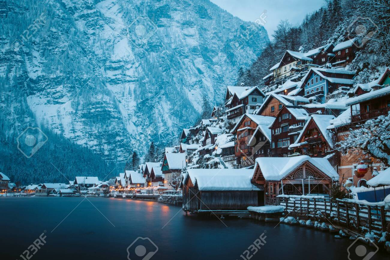 Classic postcard view of traditional wooden houses in famous Hallstatt lakeside town in the Alps in mystic twilight during blue hour at dawn on a beautiful cold foggy day in winter, Salzkammergut region, Austria - 119003218