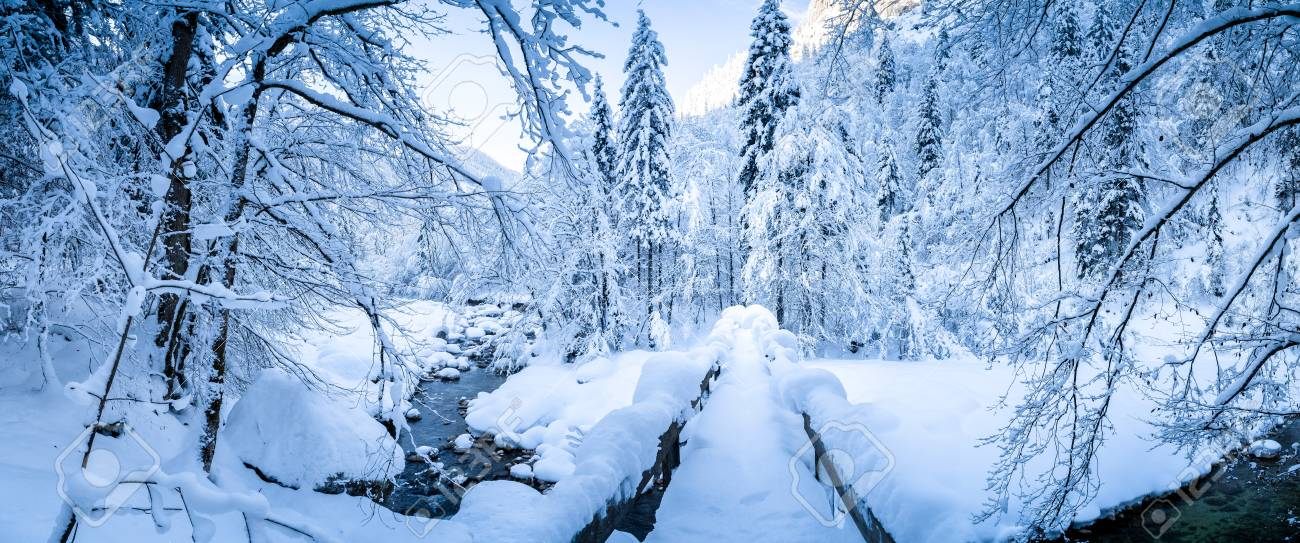 Panoramic view of scenic winter with wooden bridge leading over river bed covered in deep snow on a beautiful cold sunny day - 119087274