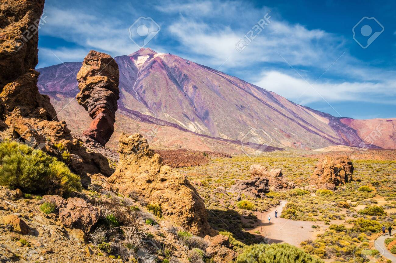 Panoramic view of unique Roque Cinchado unique rock formation with famous Pico del Teide mountain volcano summit in the background on a sunny day, Teide National Park, Tenerife, Canary Islands, Spain - 121793425