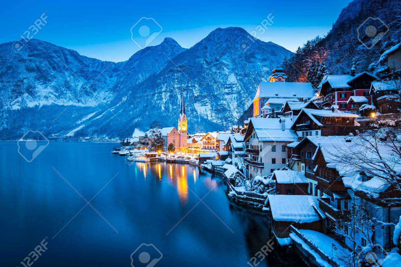 Classic postcard view of famous Hallstatt lakeside town in the Alps with beautiful Hallstattersee in mystical post sunset twilight during blue hour at dusk in winter, Salzkammergut, Austria - 121793892