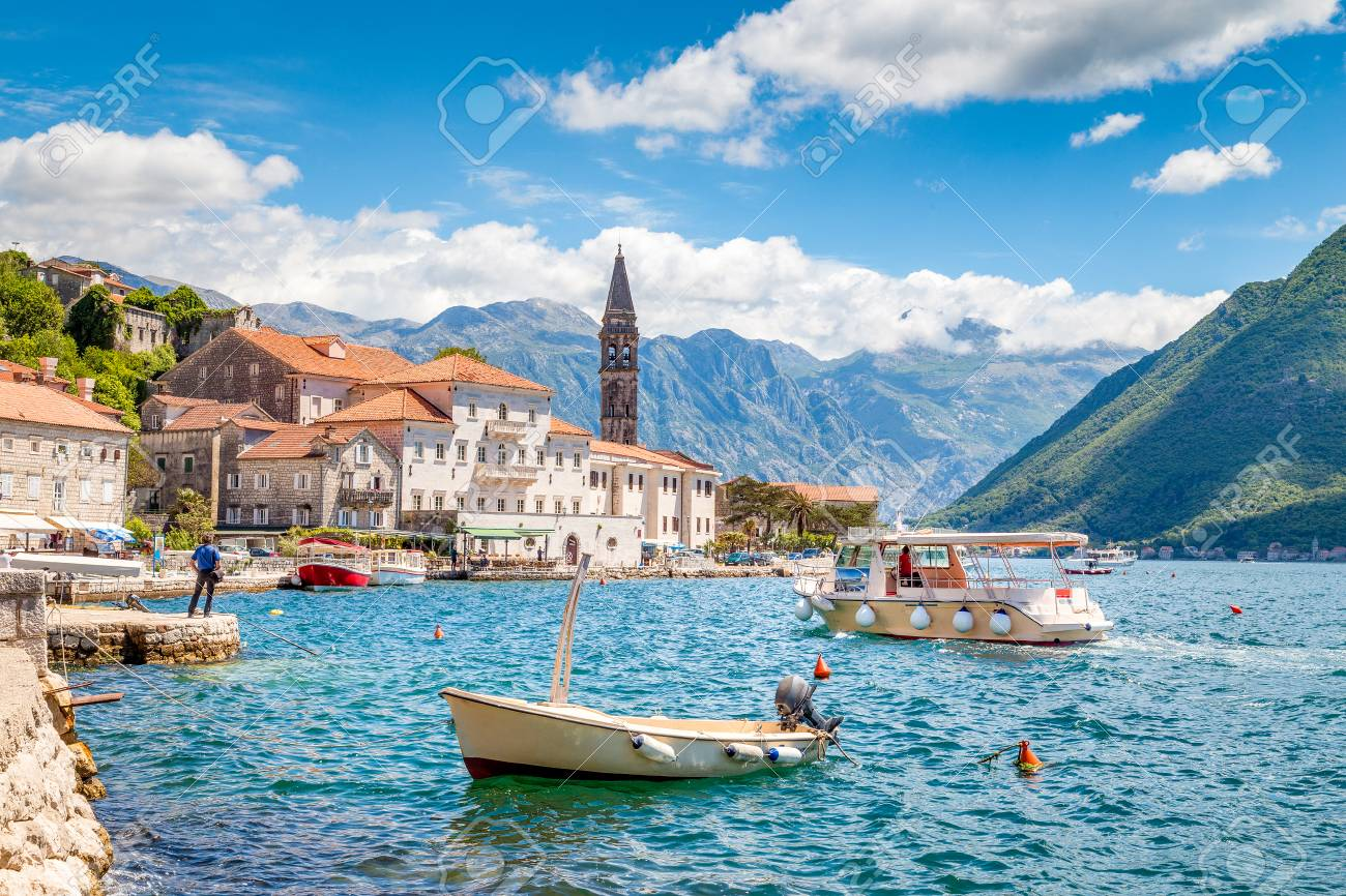 Scenic panorama view of the historic town of Perast located at world-famous Bay of Kotor on a beautiful sunny day with blue sky and clouds in summer, Montenegro, southern Europe - 121794796