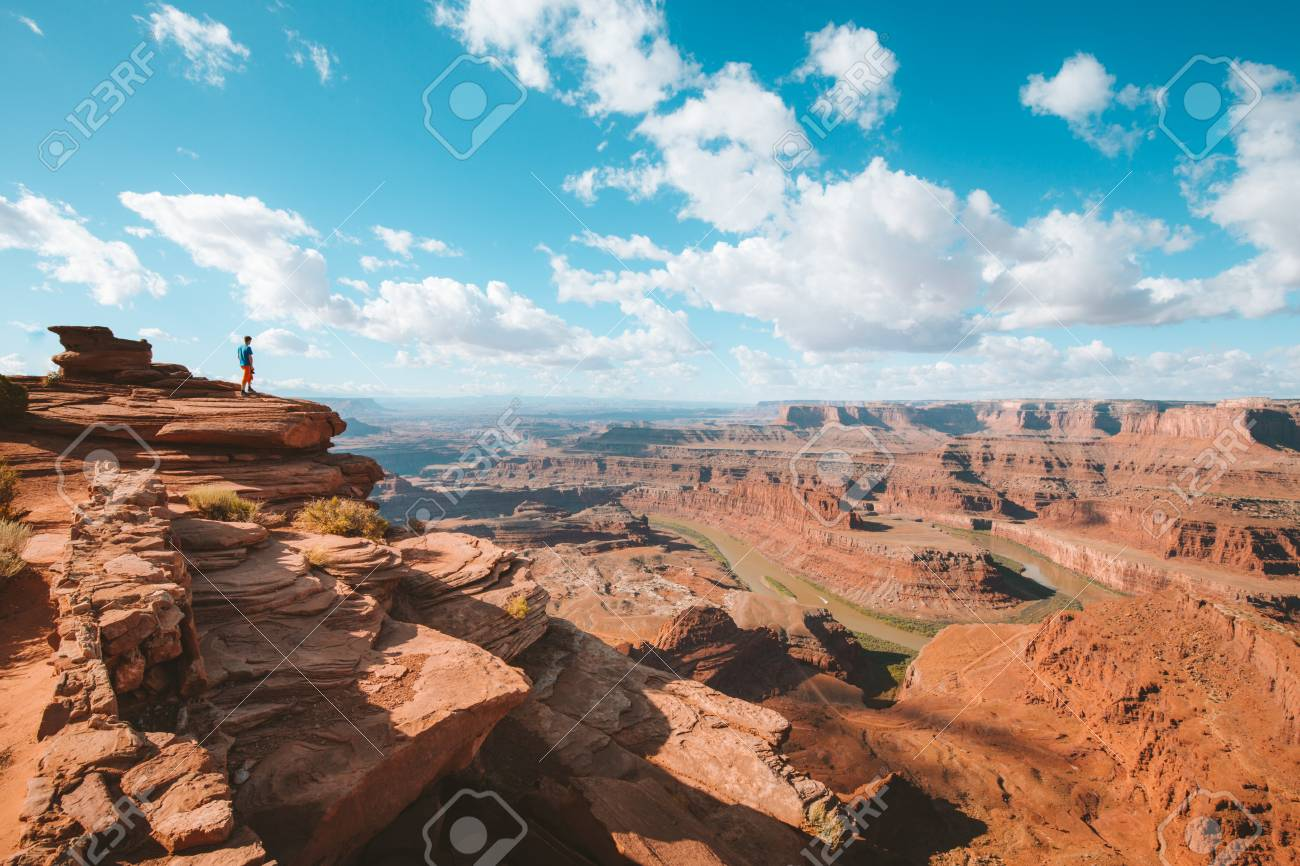 A young hiker is standing on the edge of a cliff enjoying a dramatic overlook of famous Colorado River and beautiful Canyonlands National Park in scenic Dead Horse Point State Park, Utah, USA - 121795173