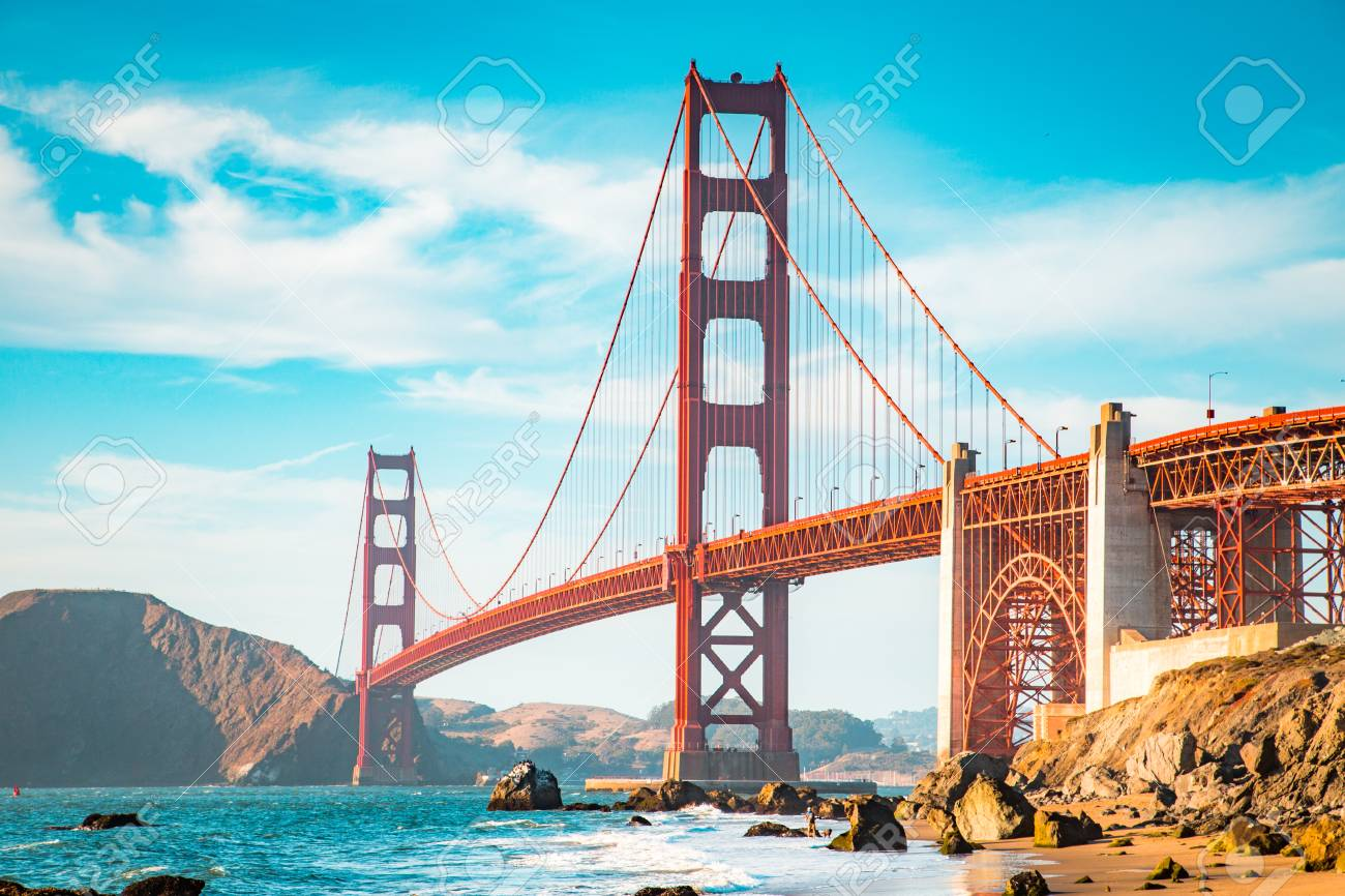 Classic view of famous Golden Gate Bridge in beautiful golden evening light on a sunny day with blue sky and clouds in summer, San Francisco, California, USA - 121795427