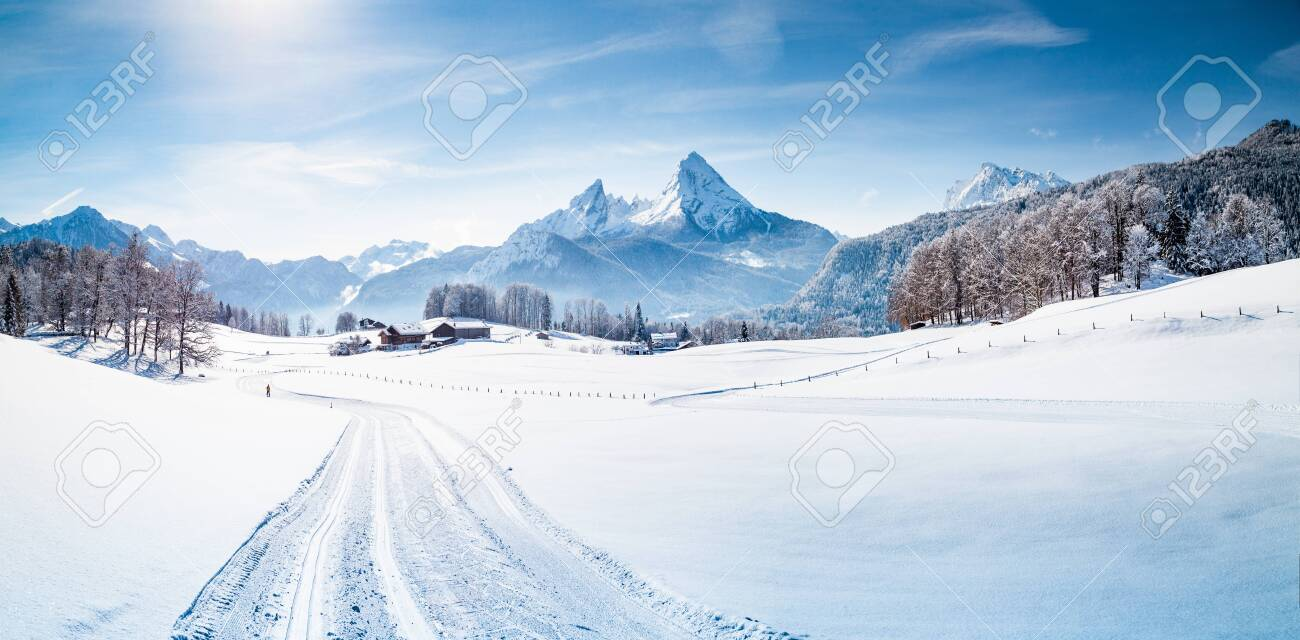 Scenic winter wonderland mountain scenery in the Alps with cross-country skiing track on a cold sunny day with blue sky and clouds - 135727047