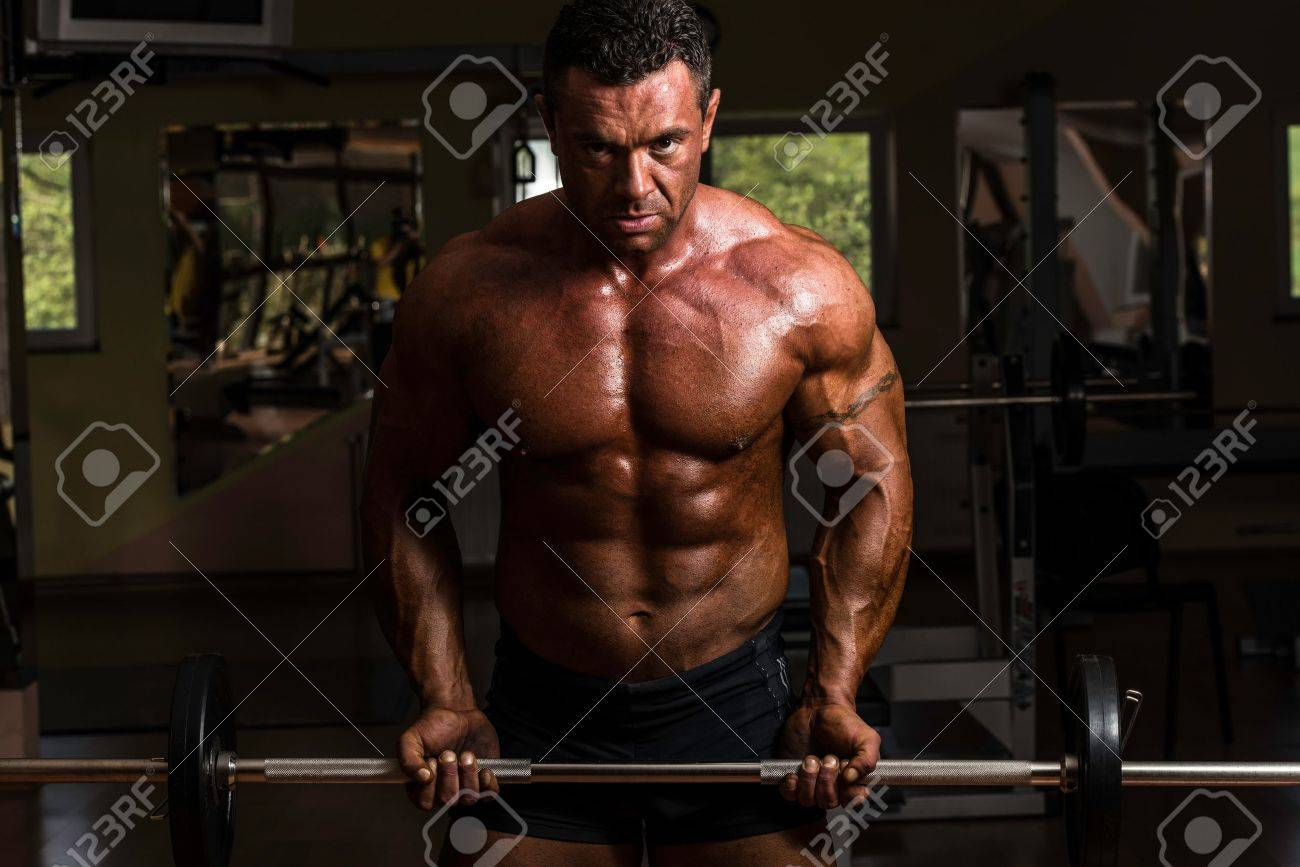 bodybuilder doing heavy weight exercise for biceps with barbell Stock Photo - 20259525