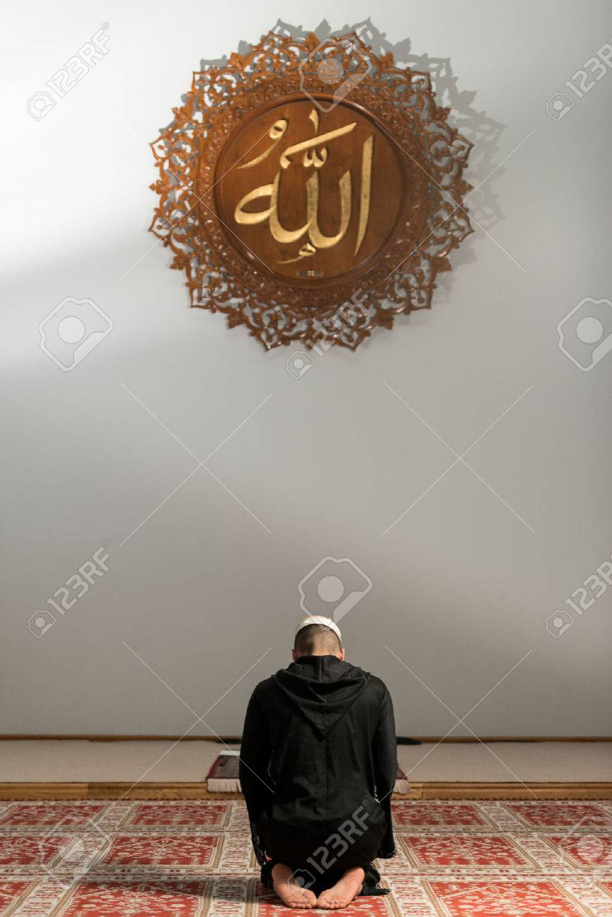 Young Muslim Guy Making Traditional Prayer To God While Wearing A Traditional Cap Dishdasha Stock Photo - 26680194