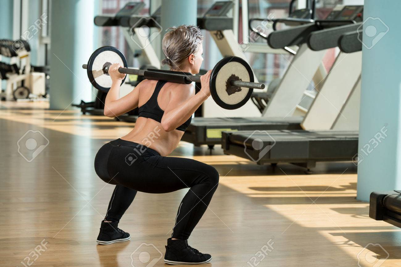 Beautiful Fit Woman Doing Barbell Squats In The Gym Stock Photo - 26940106