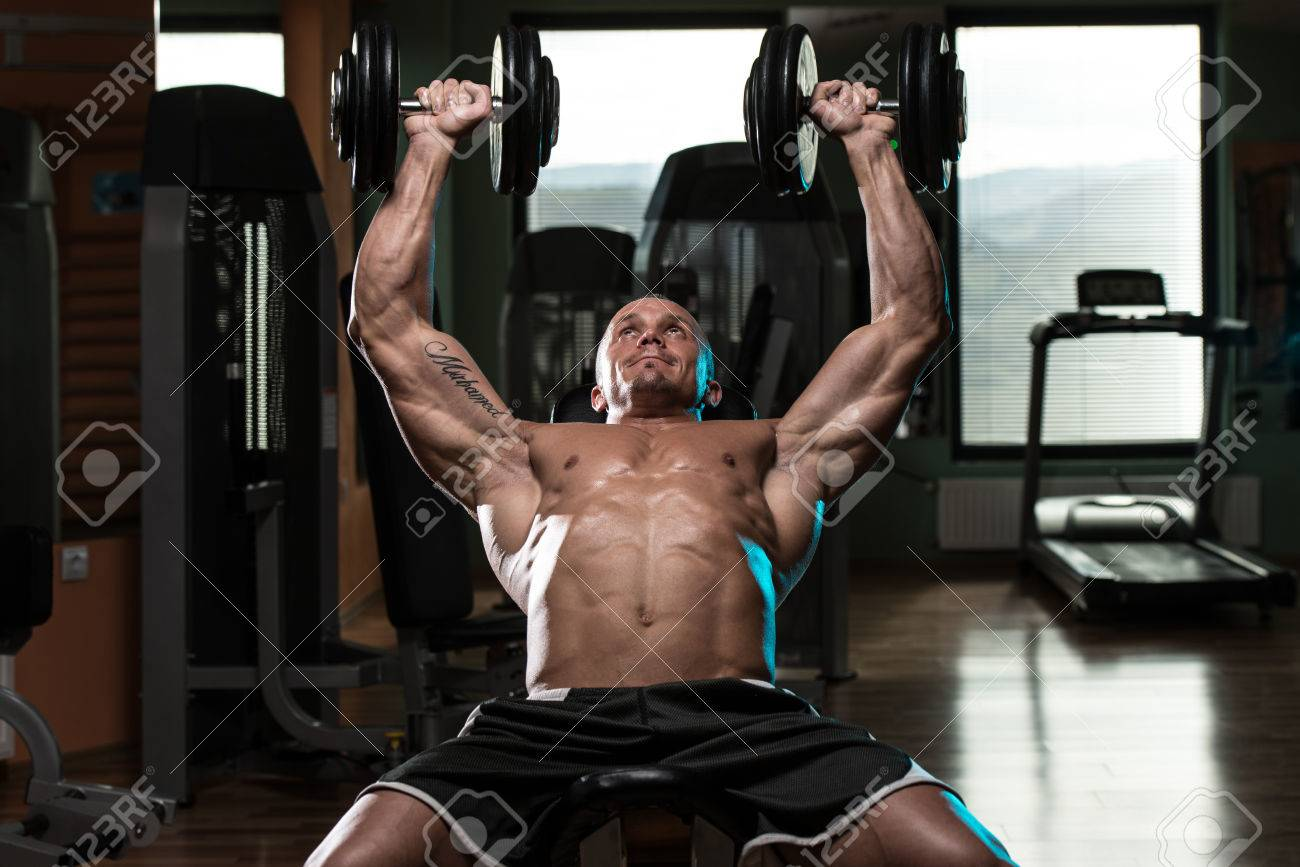 Handsome Young Man Doing Dumbbell Incline Bench Press Workout In Gym Stock Photo - 27243926