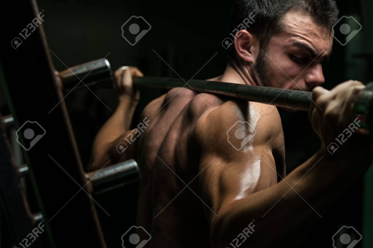 Young Man Performing Barbell Squats - One Of The Best Body Building Exercise For Legs Stock Photo - 27955180