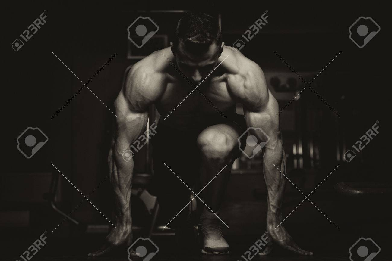 Strong Muscular Men Kneeling On The Floor - Almost Like Sprinter Starting Position Stock Photo - 28762954