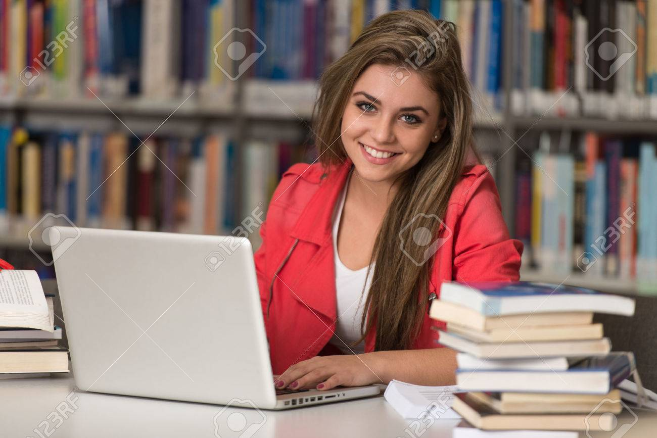In The Library - Pretty Female Student With Laptop And Books Working In A High School Or University Library - Shallow Depth Of Field Stock Photo - 33887214
