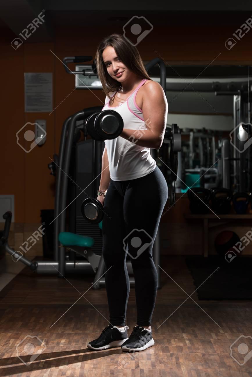Banque d images - Jeune femme faisant Heavy Weight exercice pour les biceps  avec des haltères a1a2c7e6359