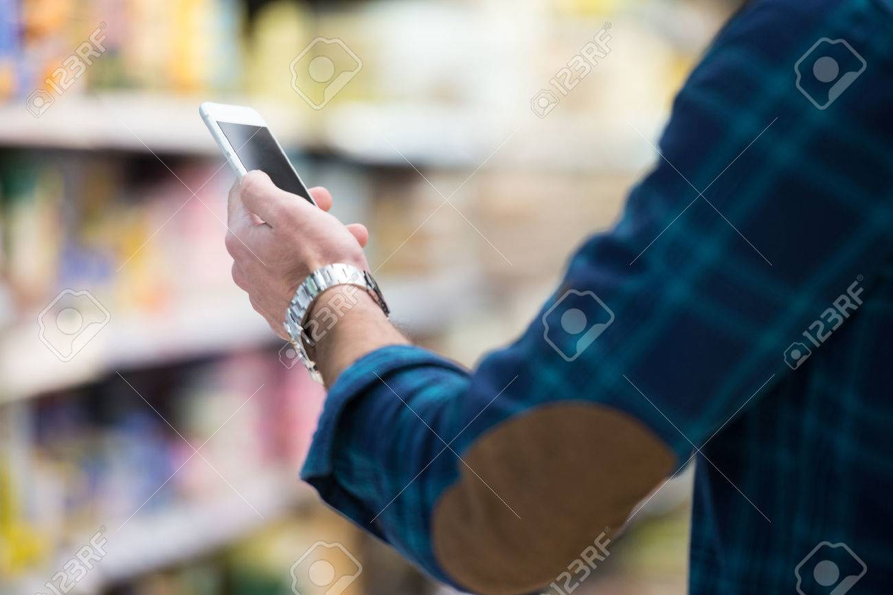Smiling Young Man Using Mobile Phone While Shopping In Shopping Store Stock Photo - 35427582