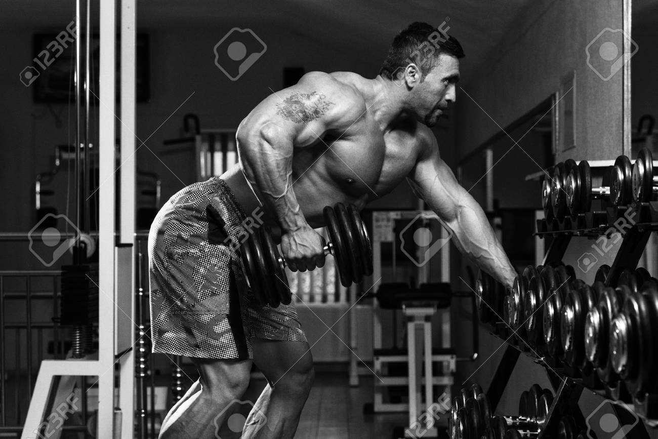 Mexican Bodybuilder Doing Heavy Weight Exercise For Back With Dumbbells Stock Photo - 35999953