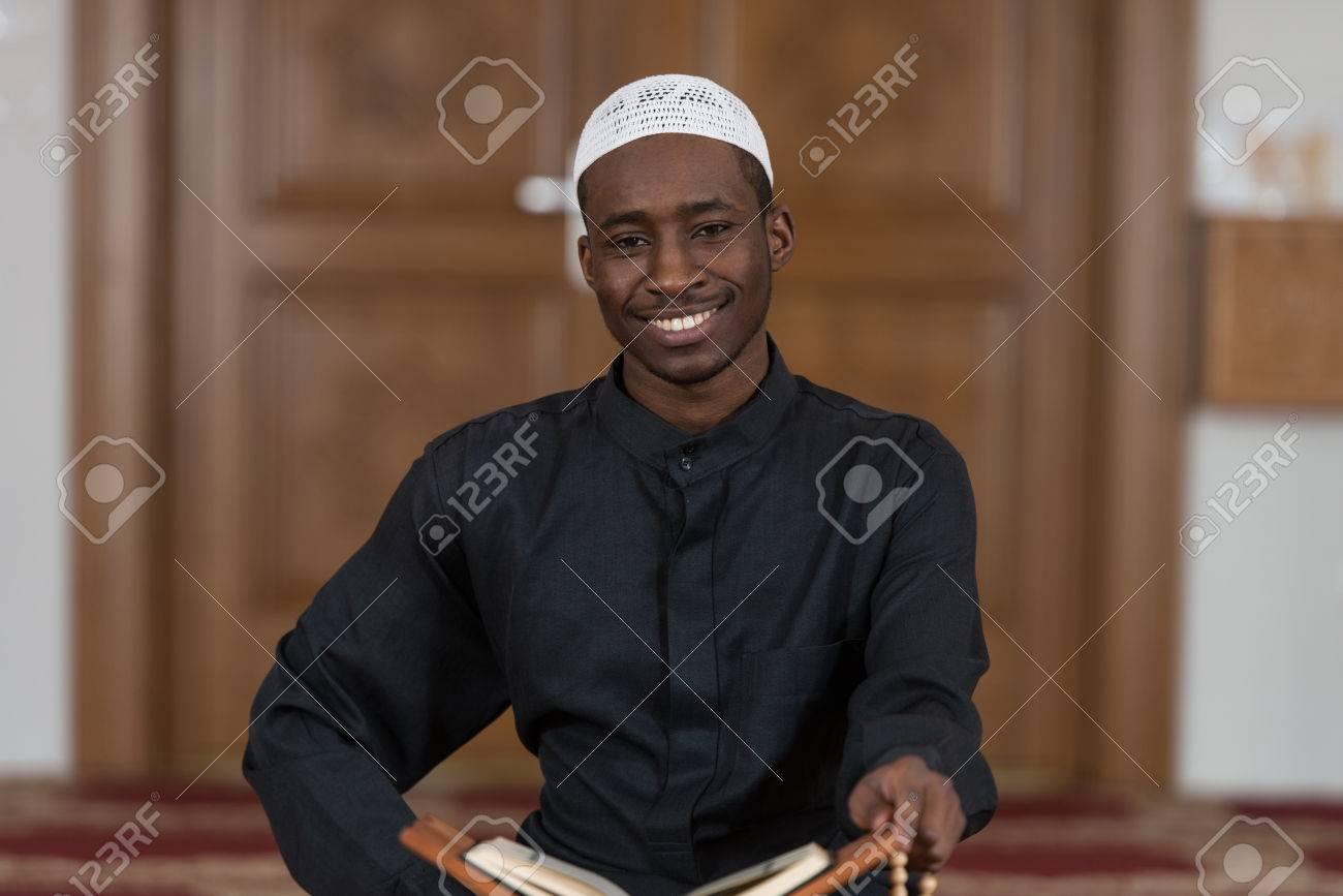 Black African Muslim Man Reading Holy Islamic Book Koran Stock Photo - 37573241